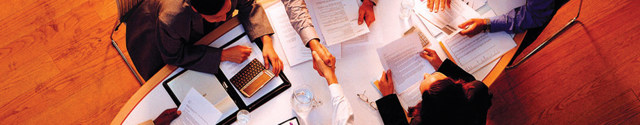 Two people shaking hands over a table during a business meeting